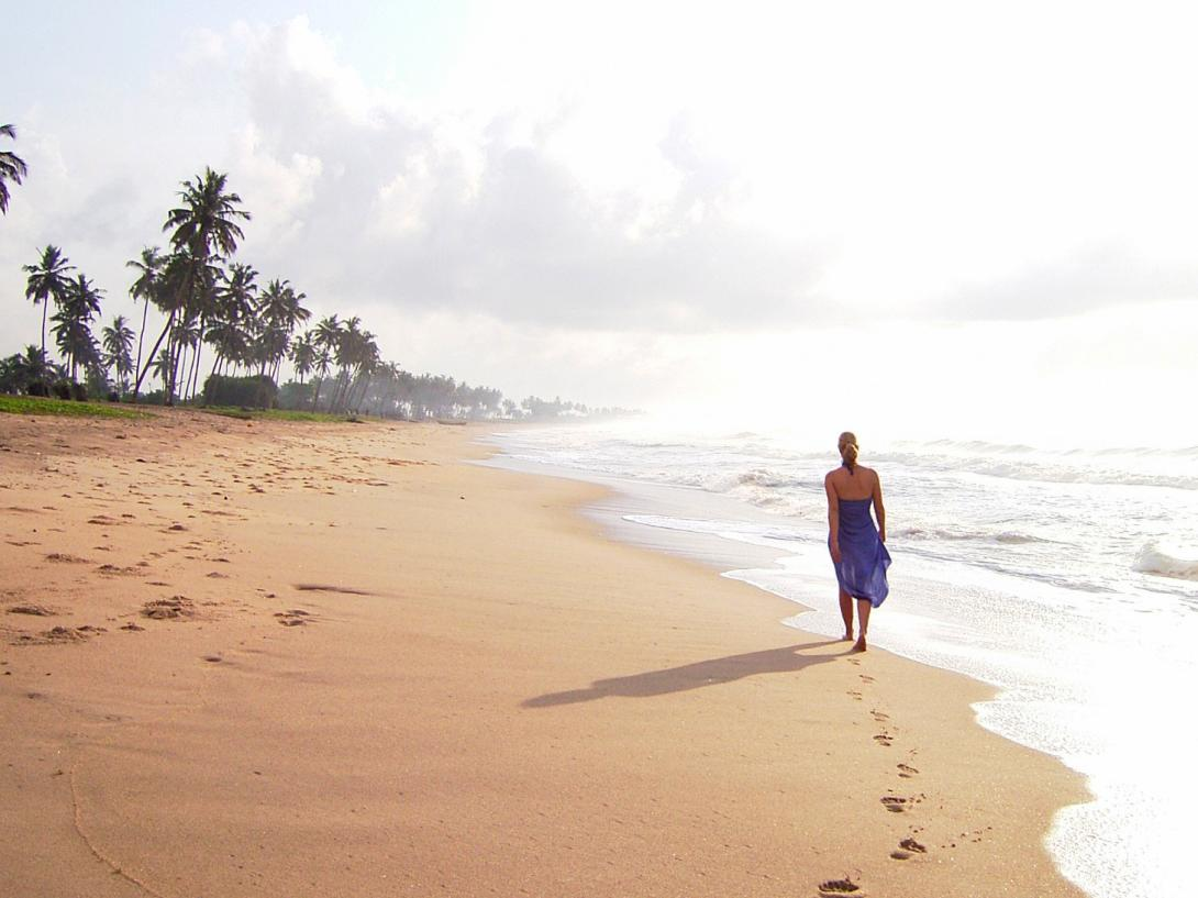 On a hot day in Ghana, a woman strolls on the beach
